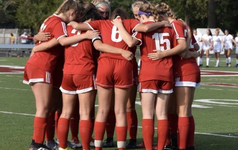 (From left to right) Alleah Ebbinghaus, Emma Secrest, Sunny Weisenberger, and Anna Deichert participate in a huddle with the starting varsity players before taking the field against Westerville North on Aug. 8. The game ended in a 3-0 win for North. <i>Photo courtesy of Laney Walden</i>