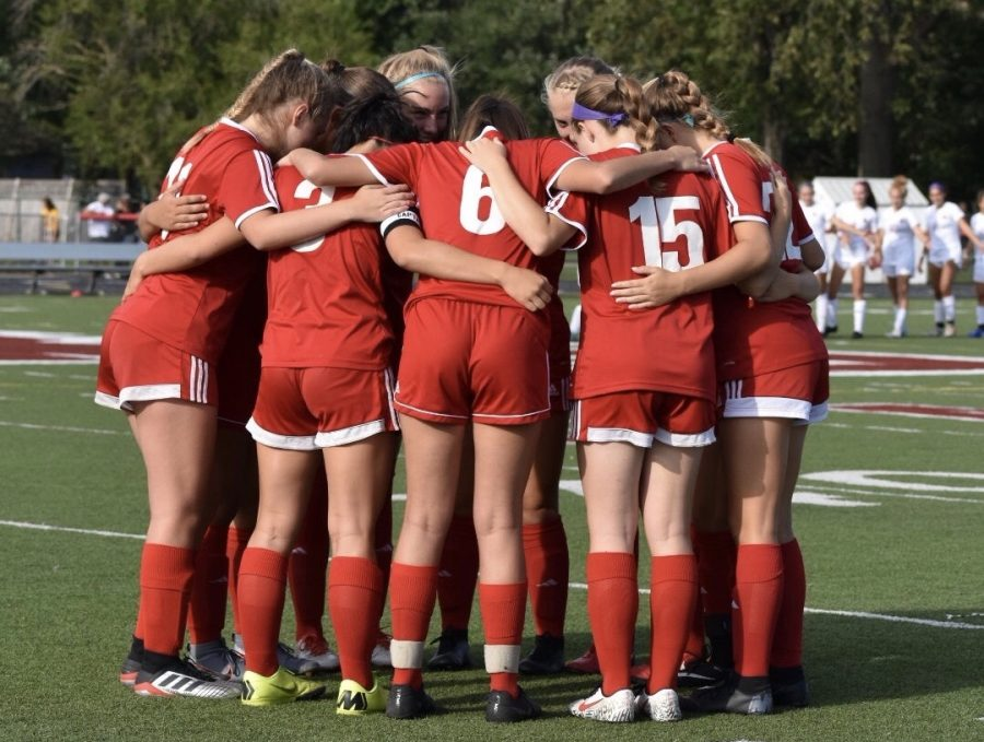 (From left to right) Alleah Ebbinghaus, Emma Secrest, Sunny Weisenberger, and Anna Deichert participate in a huddle with the starting varsity players before taking the field against Westerville North on Aug. 8. The game ended in a 3-0 win for North. Photo courtesy of Laney Walden